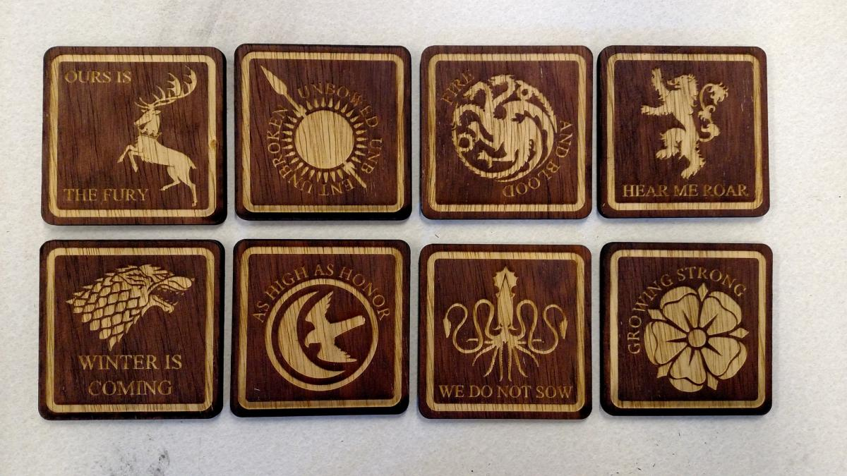 laser cut wooden coasters for houses baratheon, martell, targaryen, lannister, stark, arryn, greyjoy, and tyrell